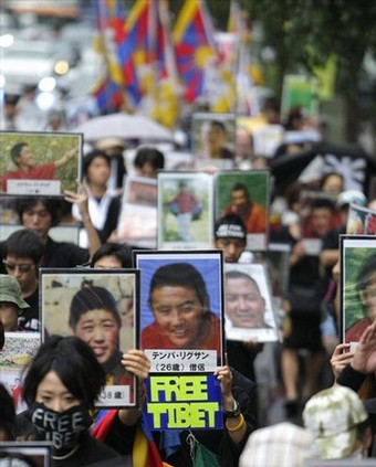 Pro-Tibet protesters carry portraits of Tibetans allegedly killed during protests in Tibet and march without shouting slogans through Tokyo streets Sunday, Aug. 24, 2008. About 200 people take part in the silent march in an attempt to create the atmosphere of funeral procession, marking the final day of Beijing Olympics. (Photo: Shizuo Kambayashi/AP)